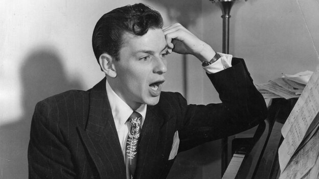 American singer and actor Frank Sinatra sits at the piano.