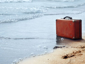 Lost luggage on a beach.