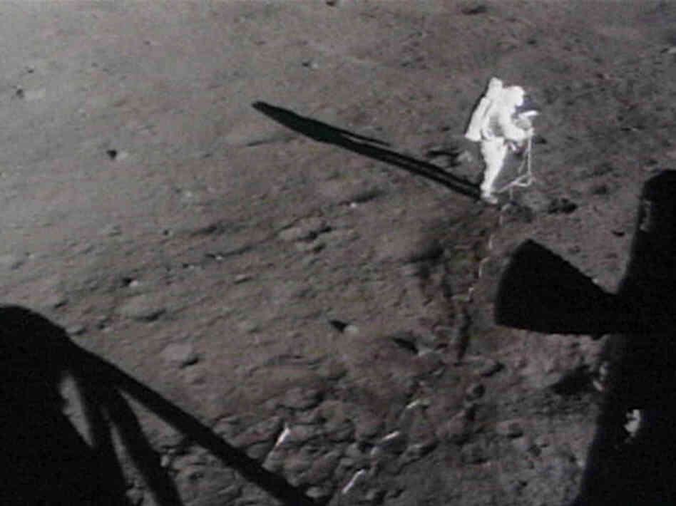 Astronauts move the lunar camera onto a tripod on the moon.