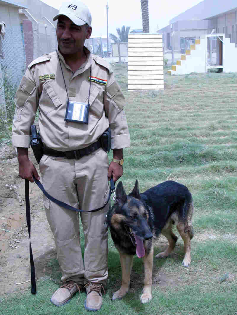 An Iraqi police officer in the Iraqi National Canine Program in Baghdad stands with his dog.