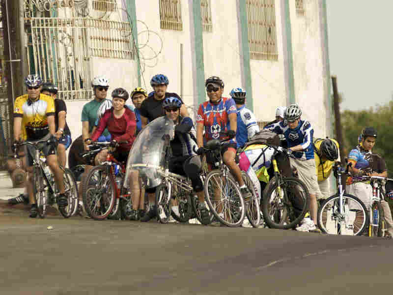 Tijuana bicyclists reach the top of a hill.