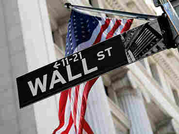 U.S. flag behind Wall Street sign.