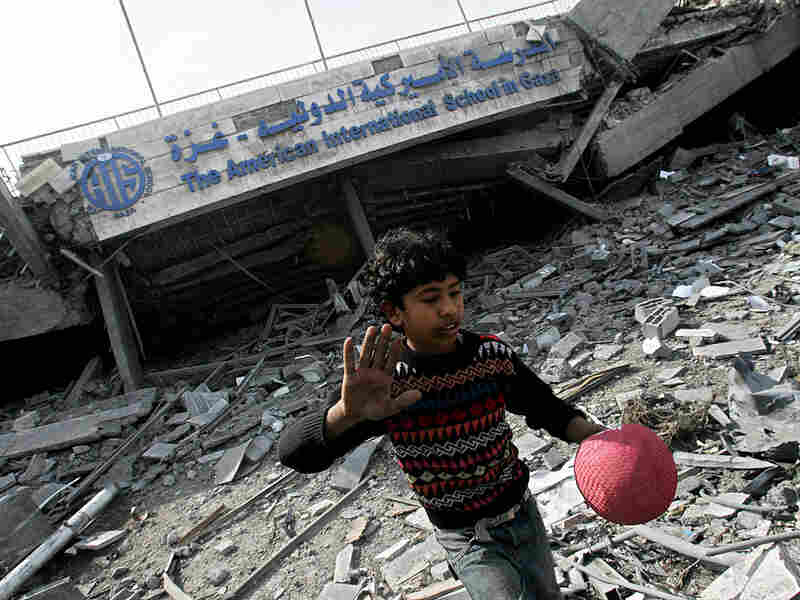 A Palestinian boy walks pas5 the rubble of the American International School.