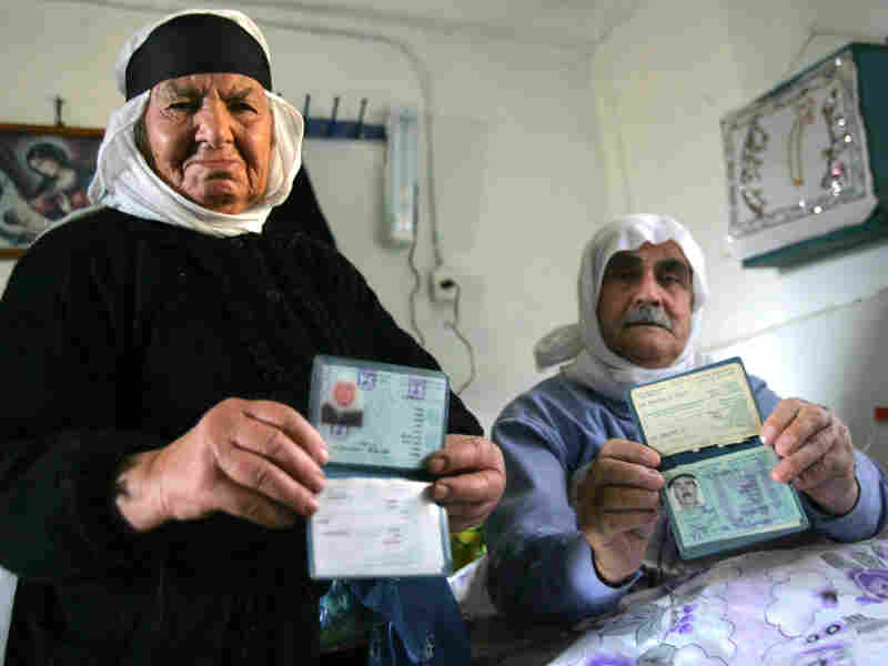 Two Ghajar residents display their Israeli identity documents in 2006.