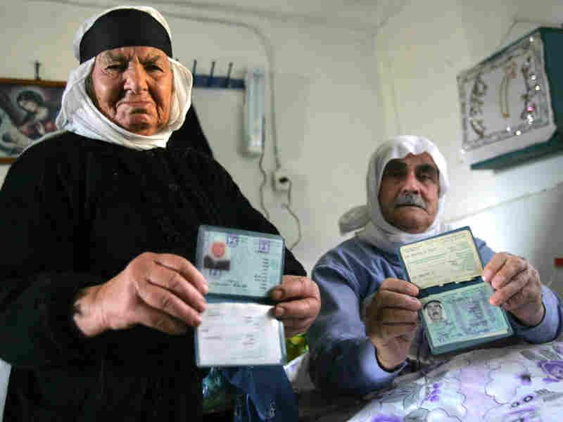 Two Ghajar residents display their Israeli identity documents in 2006.