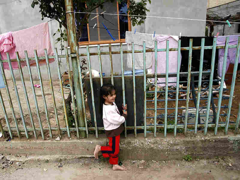 A barefoot girl stands outside her home in Ghajar, May 3, 2009.