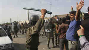 Wide: Iranian anti-riot policeman raises his baton to disperse protesters at an opposition rally.