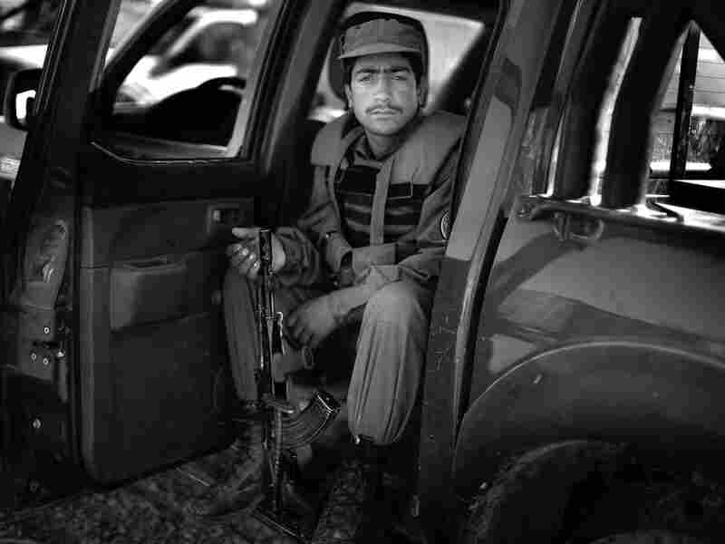 An Afghan policeman sits in the backseat of his truck in Lashkar Gah in Helmand province.