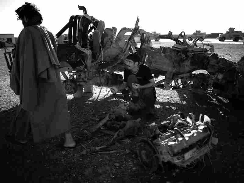 Two men look through the wreckage of a Afghan National Police truck that was hit with an IED.