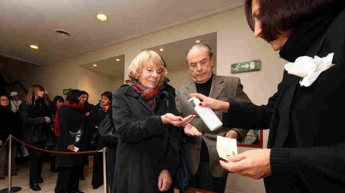 Wide: A couple uses hand sanitizer before entering a theater in Buenos Aires, Argentina.