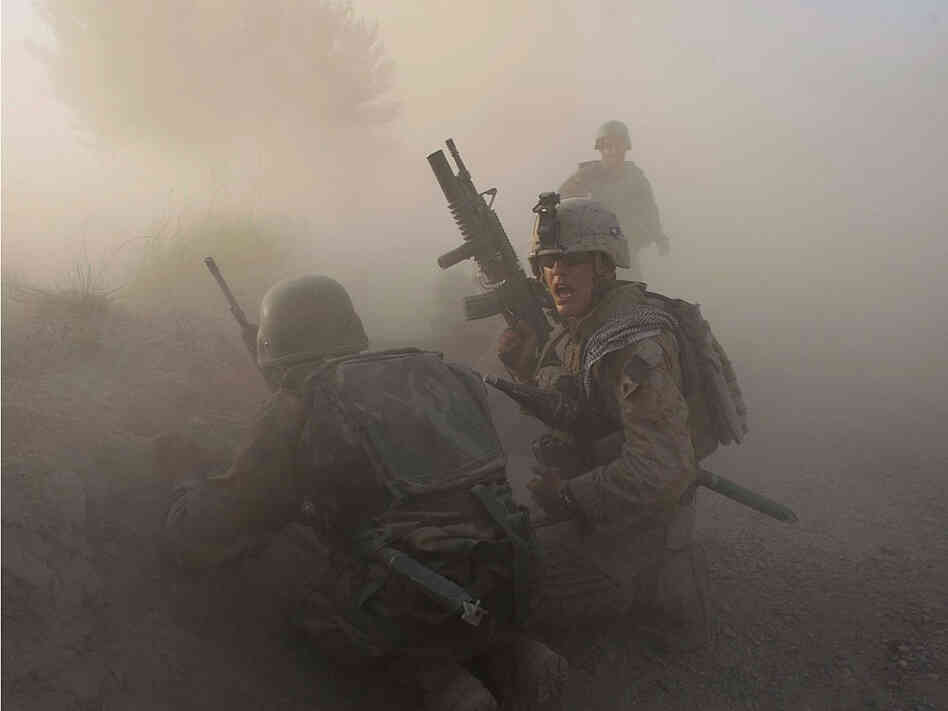 A U.S. Marine and an Afghan soldier react after an IED explodes in Mian Poshteh, Afghanistan.