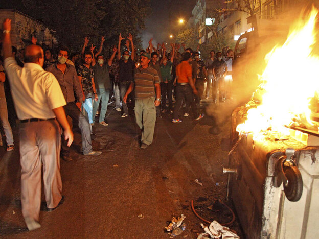 Anti-government protesters chant slogans as  a public trash dumpster is set on fire during a protest in Tehran, Iran, July 30, 2009. The Iranian government has banned foreign media from covering some events in Iran; this image was taken by an individual not employed by The Associated Press and obtained by the AP outside Iran.
