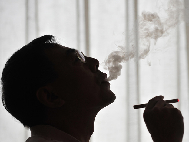 The inventor of the electronic cigarette, Hon Lik smokes his invention in Beiijng.