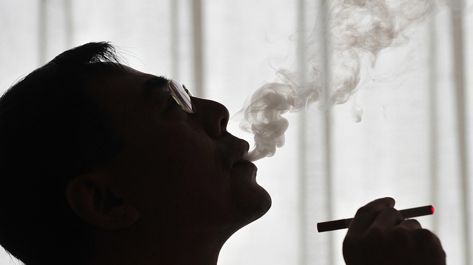 The inventor of the electronic cigarette, Hon Lik smokes his invention in Beiijng on May 25, 2009. Also known as an 'e-cigarette', the battery-powered device is designed as an alternative to cigarettes, cigars and pipes, and provides inhaled doses of nicotine by delivering a vaporized propylene glycol/nicotine solution, while also providing the physical sensation and flavors similar to inhaled tobacco smoke.