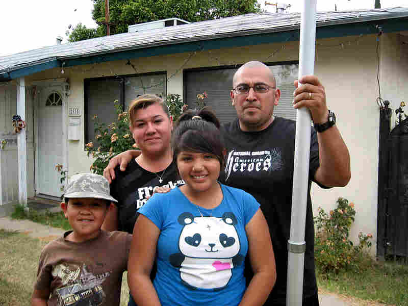 Leonard and Sylvia Contreras stand in the front yard of their former rental house in Fresno, Calif.