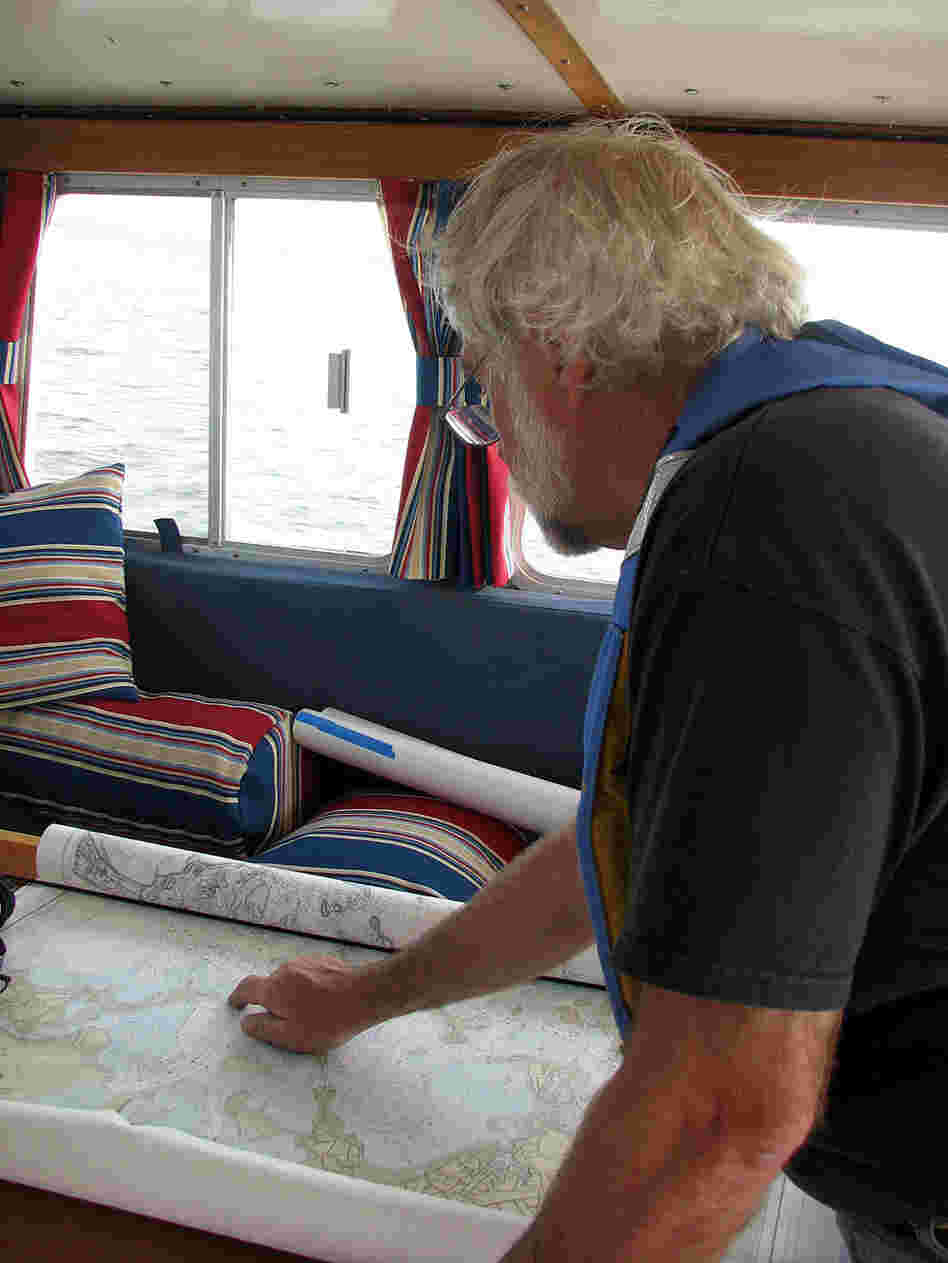 Captain John Williamson examines a chart of Massachusetts Bay.