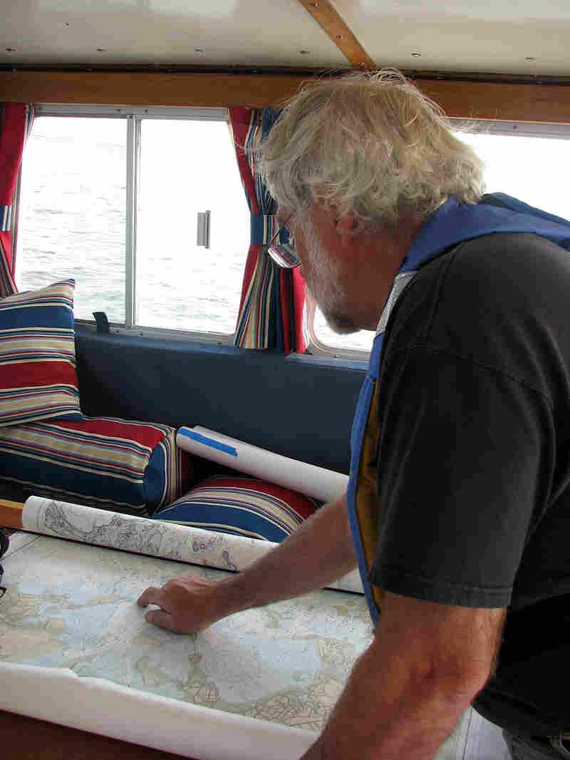 Captain John Williamson examines a chart of Massachusetts Bay.