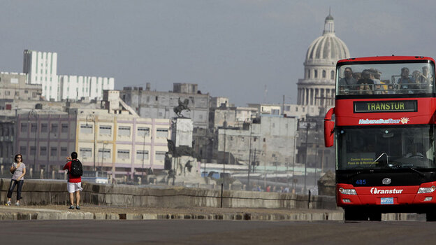 Tourists take photos as a sightseeing bus drives by along Havana's Malecon