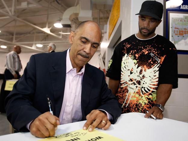 Former Indianapolis Colts coach Tony Dungy signs an autograph for Dwight Cobbs at a workshop for ex-offenders seeking jobs, in Indianapolis.