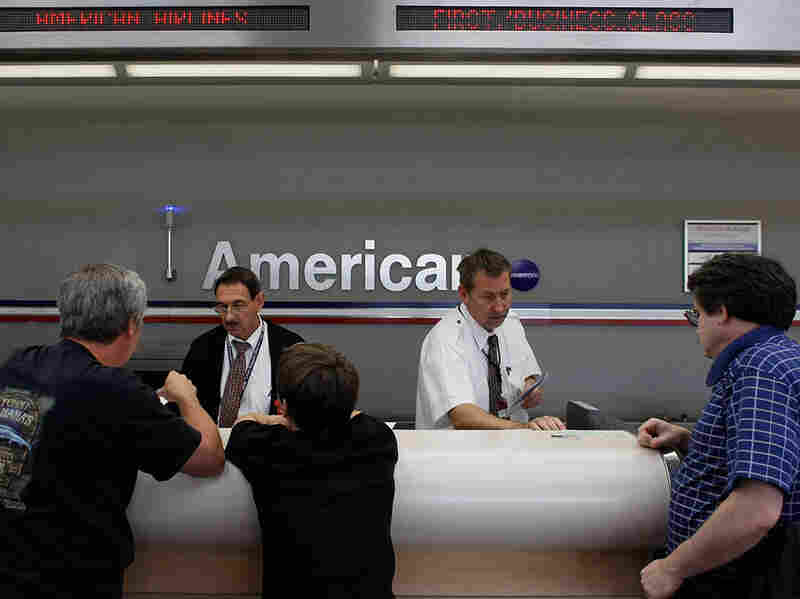 Passengers check in at an American Airlines ticket counter at Fort Lauderdale International Airport.