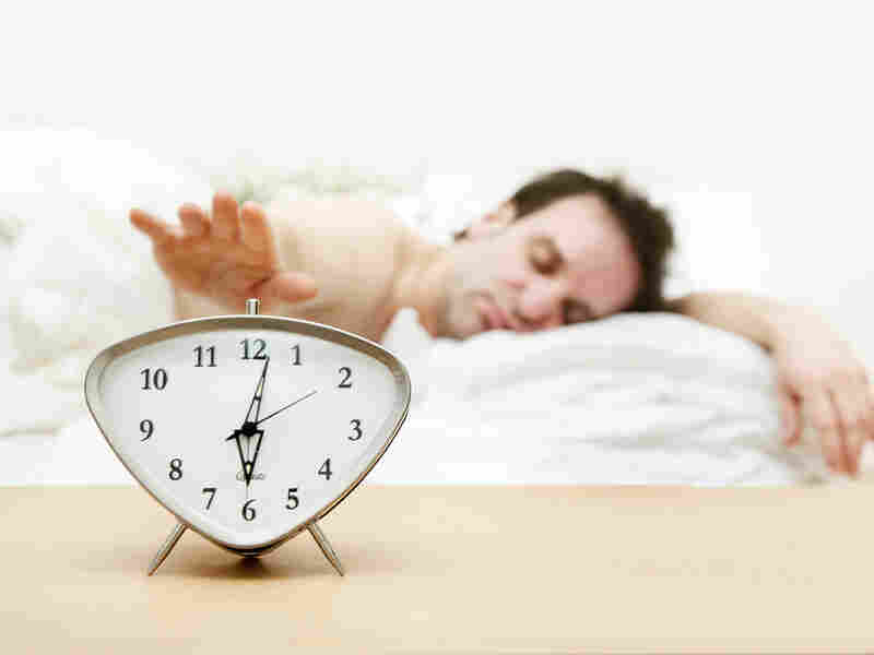 A man hits the snooze button on his alarm clock.