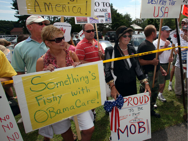 People protesting proposed health care reform outside of the high school where President Obama was conducting a town meeting on Aug. 11, 2009, in Portsmouth, N.H.