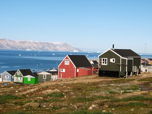 A row of houses along the fjord in Qaanaaq, Greenland.