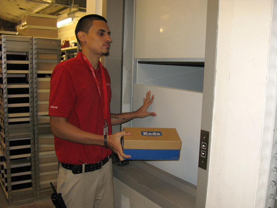 "Eric Delgado, a ""runner"" in the shoe department at the new J.C. Penney in midtown Manhattan, loads shoes onto a dumbwaiter, which transports them to the salesroom floor one flight up.  When a salesperson needs a pair of shoes for a customer, it's Delgado's job to dash around a lower floor stockroom and send them up."