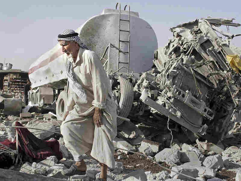 Man walks past rubble after double truck bombing in northern Iraq