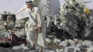 Wide: Man walks past rubble after double truck bombing in northern Iraq