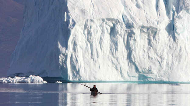 wide: A hunter paddles his kayak near Qaanaaq, Greenland.