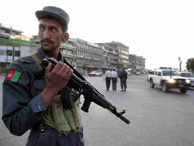 An Afghan policeman stands guard in the downtown market area in the capital city of Kabul.