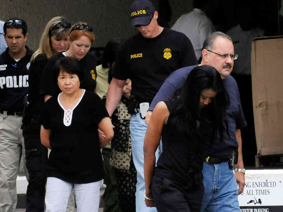 Federal agents escort suspects out of the FBI offices July 29, 2009 in Houston.