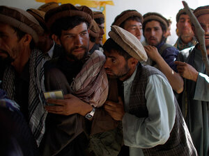 Afghan police try to control the line of men waiting
