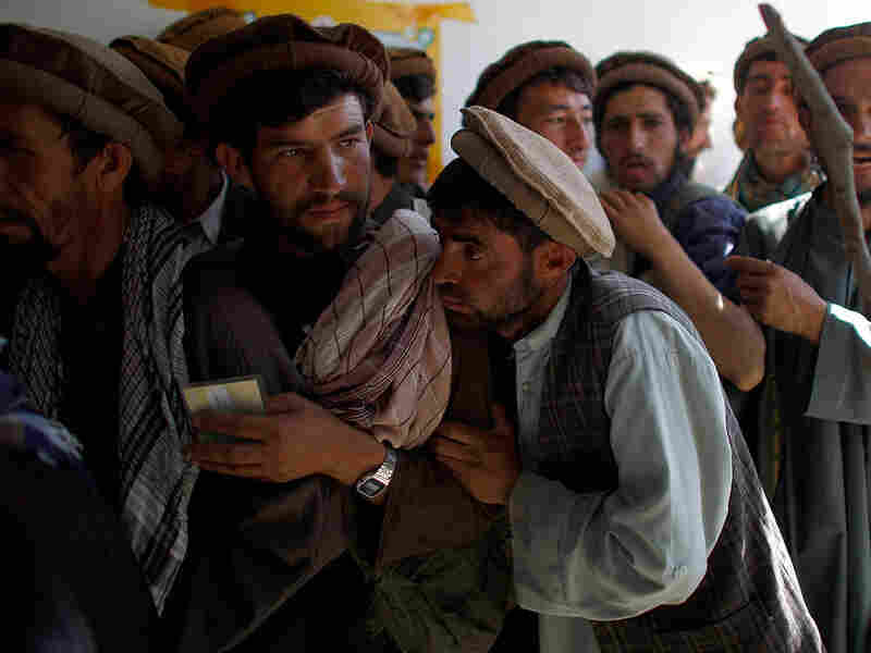 Afghan police try and control the line of men waiting