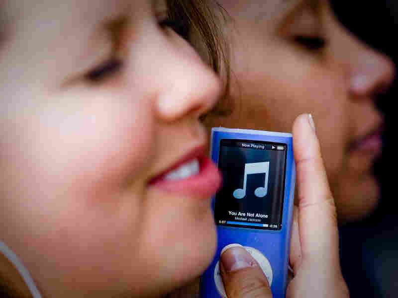 A smiling girl listens to music on her iPod.