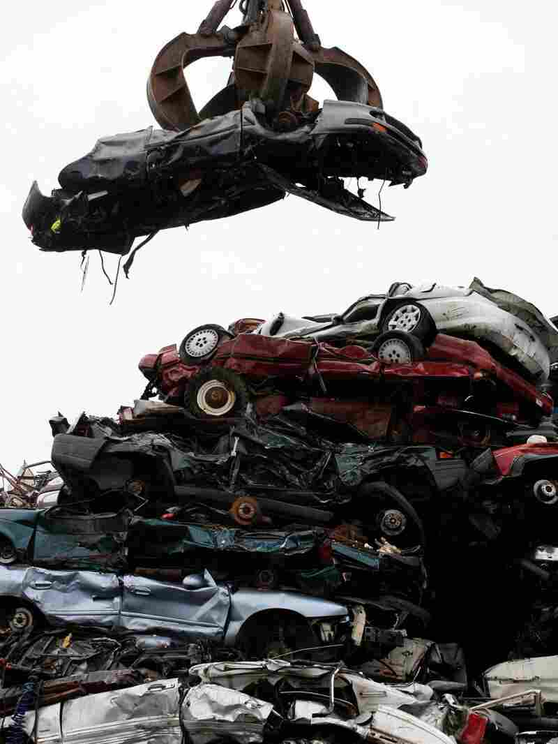 A car dangling over a wreckage yard. Mark Lennihan/AP