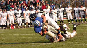 A high school football player is tackled.