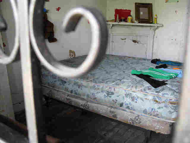 The front room of this deteriorating house has become a bedroom for one squatter.