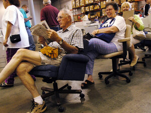 Howard Cross of Grass Valley, Calif., reads the paper in the desk chair he plans to buy.