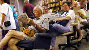 w-Howard Cross of Grass Valley, Calif., reads the paper in the desk chair he plans to buy.