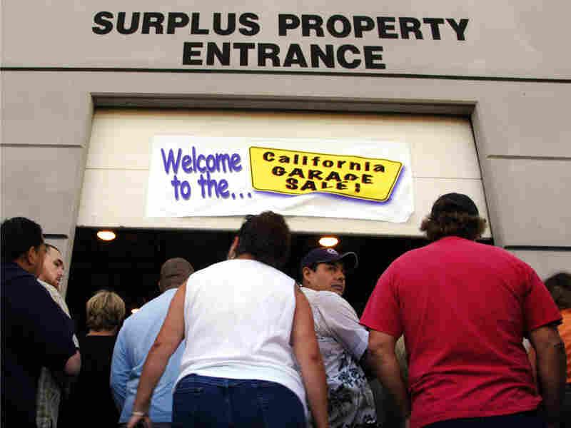 "People wait for the start of California's ""Garage Sale"" Thursday in Sacramento, Calif."