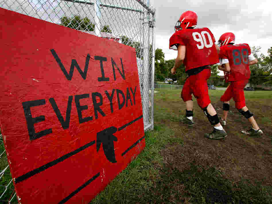 'Win Everyday': Aplington-Parkersburg High football players run past a sign on the practice field