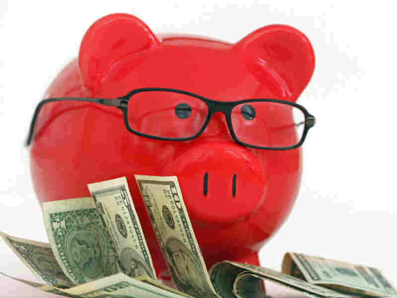 A red piggy bank wearing glasses and standing on money. iStockphoto.com