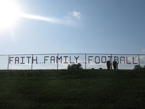 Red plastic cups stuck in a chain-link fence spell out faith, family, football.