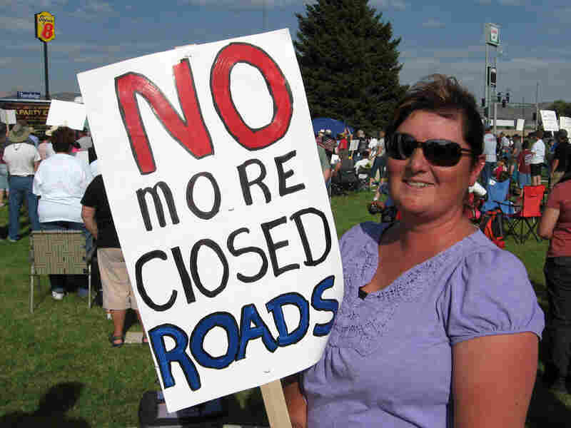 Sherry Hussey holds a sign: 'No More Closed Roads'