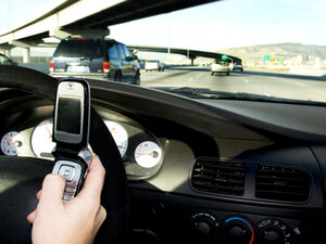 A person texts while driving on the freeway.