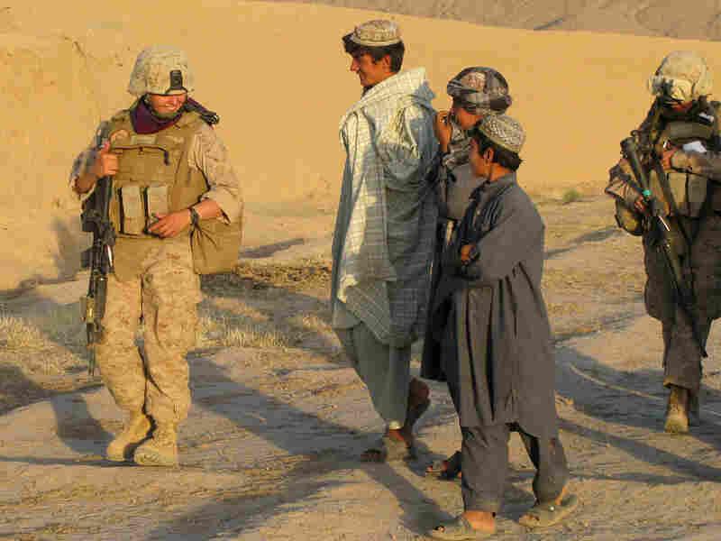 Marine Lance Cpl.  Mary Shloss, left, talks with Afghan boys in Khwaji Jamal village.