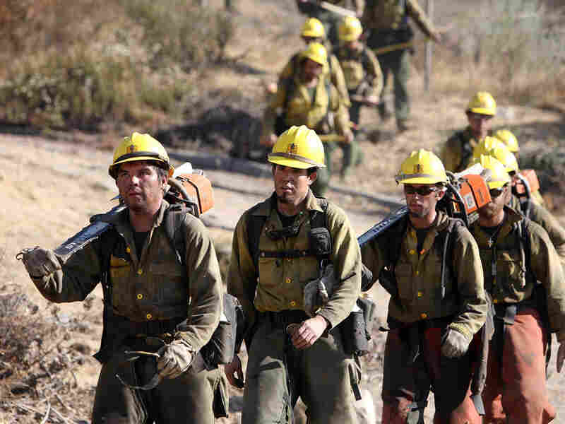U.S. Forest Service workers hike down a hill while fighting the Station Fire in Tujunga, Calif.