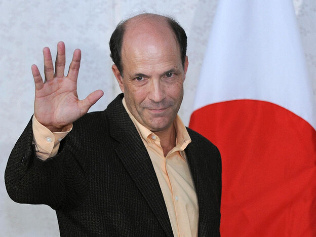 John Roos, the new U.S. ambassador to Japan, waves to journalists Aug. 19 after his arrival at Narita International Airport outside Tokyo. The new ruling party, the Democratic Party of Japan, has traditionally opposed what it calls Japan's subservience to the United States and criticized the U.S. military presence in the country.